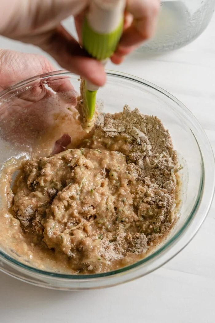 Mixing wet and dry baking ingredients together in a large glass mixing bowl.