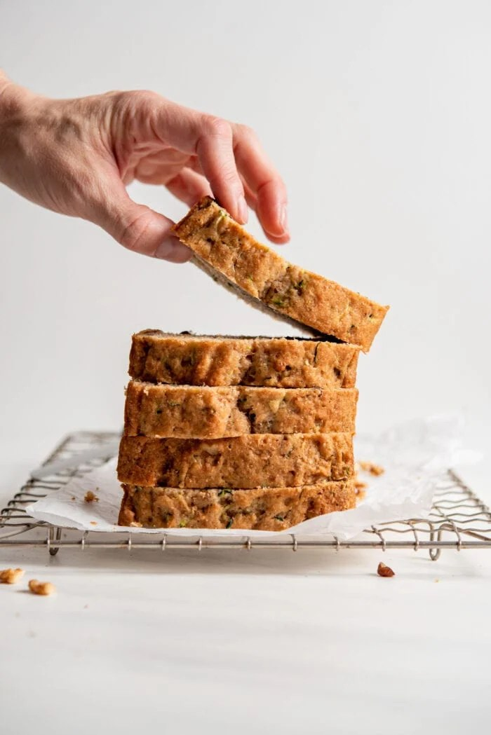 Hand picking up a slice of zucchini loaf from a stack of slices sitting on a cooling rack.