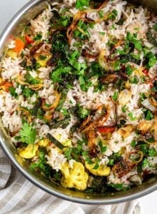 Overhead view of vegetable biryani topped with onions and herbs in a pot.