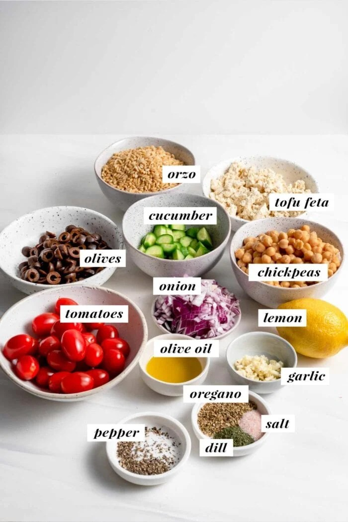 Visual of ingredients needed for making an orzo salad labelled with text overlay.