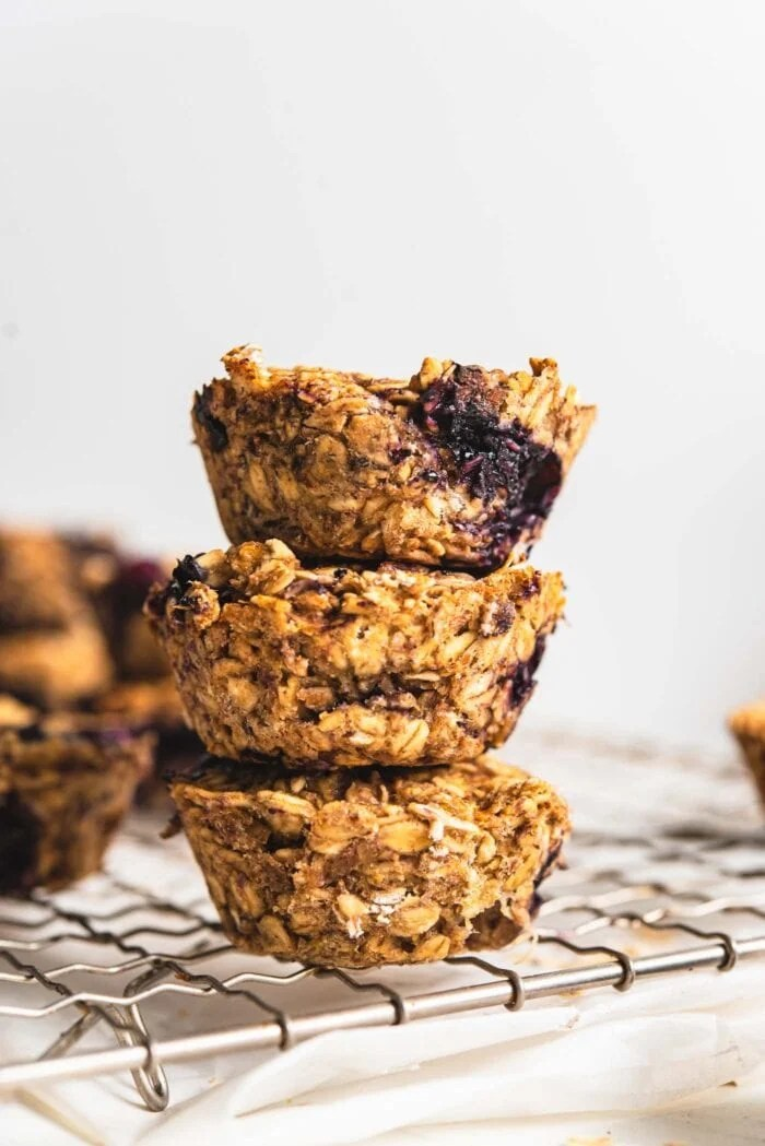 Stack of 3 baked blueberry baked oatmeal cups on a cooling rack.