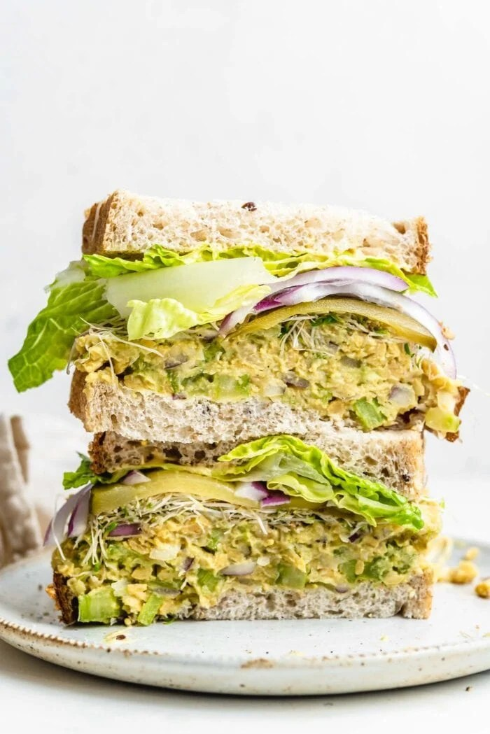 Two halves of a chickpea sandwich with sprouts and lettuce stacked on top of each other.