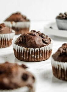 A double chocolate muffin in a cupcake liner sitting on a marble surface with a number of other muffins around it out of focus.