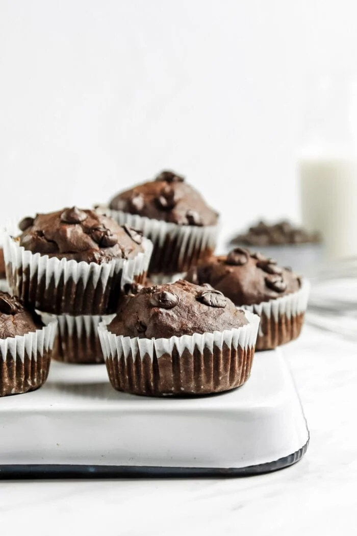 A number of chocolate muffins with chocolate chips in them sitting on a flipped over baking pan on a marble surface.
