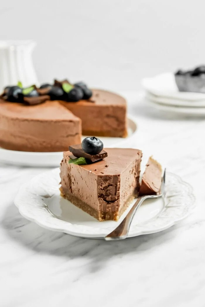 Slice of chocolate cheesecake with a fork resting beside it on a small decorate plate and a whole cheesecake in the backgorund.