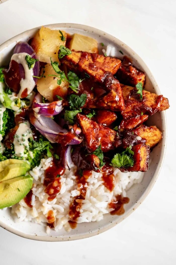 Close up overhead view of a bowl of rice, bbq tofu, avocado, red onion and pineapple.