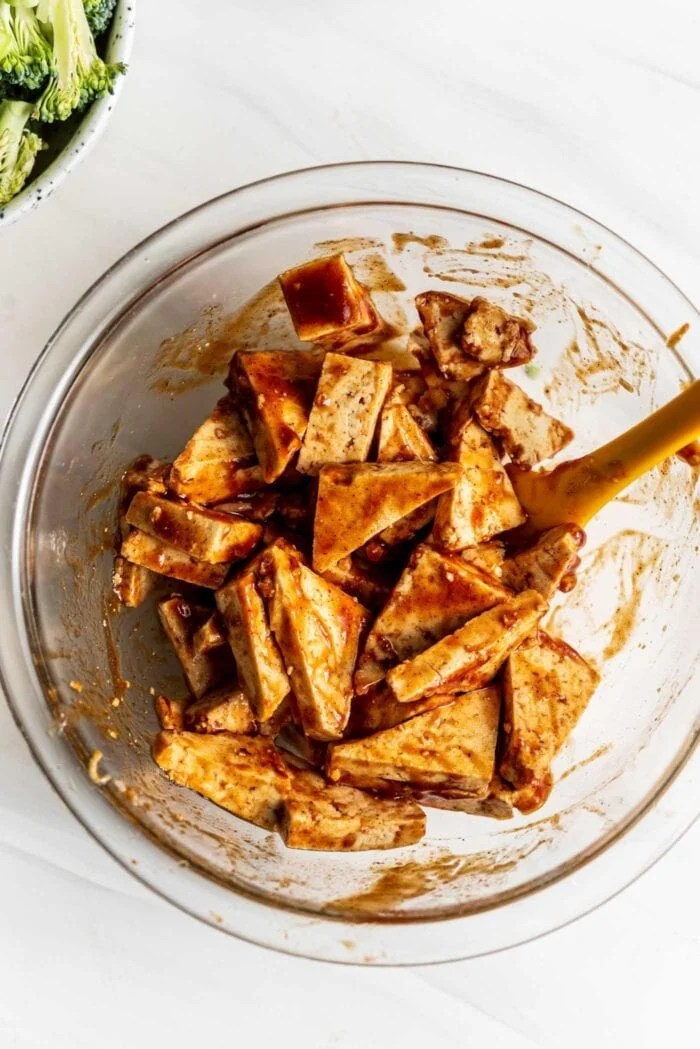 Tofu cut into triangles in a bowl with bbq sauce.