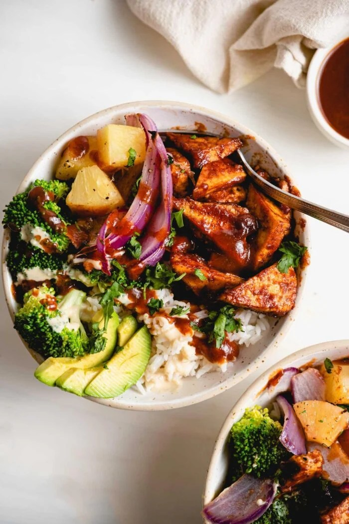 Overhead view of a bowl of rice, bbq tofu, avocado, red onion and pineapple.