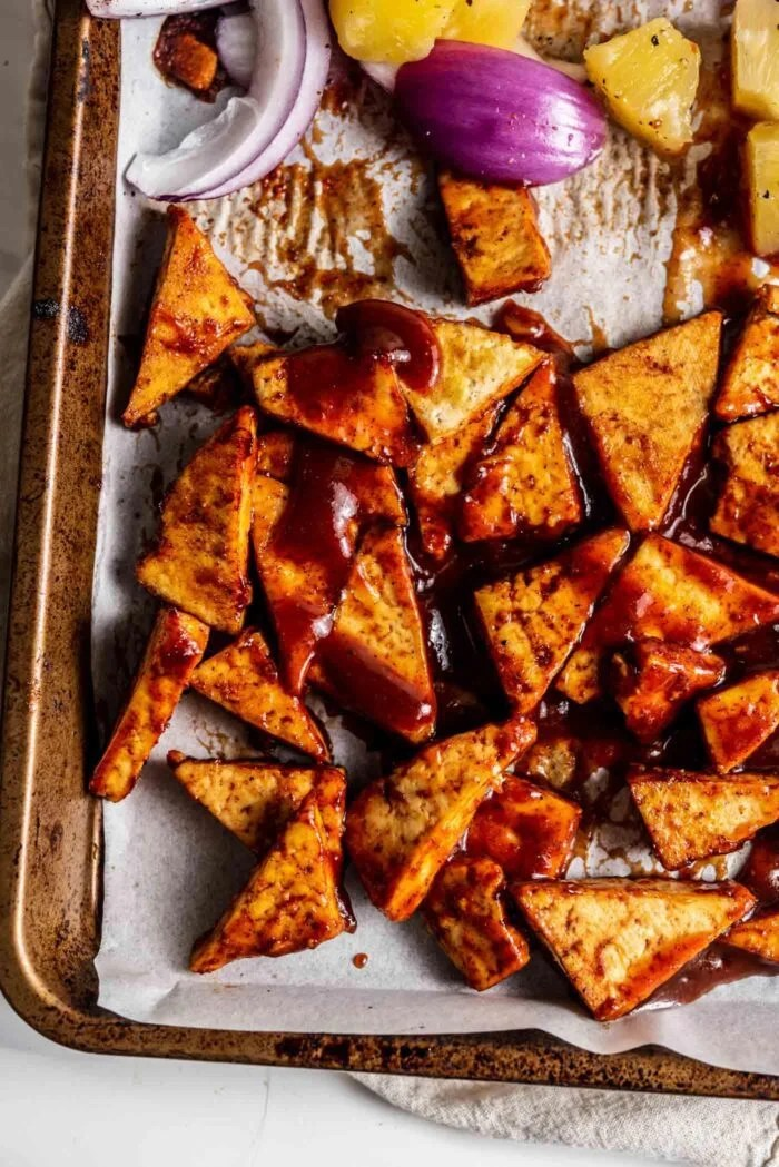 Tofu triangles mixed with bbq sauce on a parchment paper-lined baking tray.