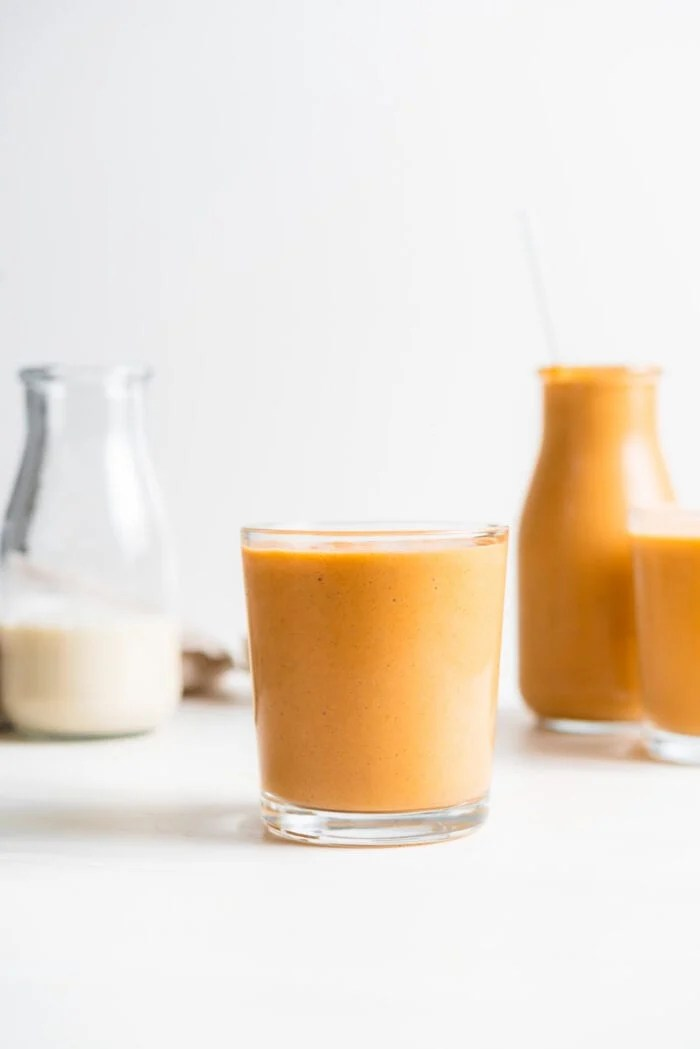 Carrot smoothie in a glass with two more smoothies in the background.