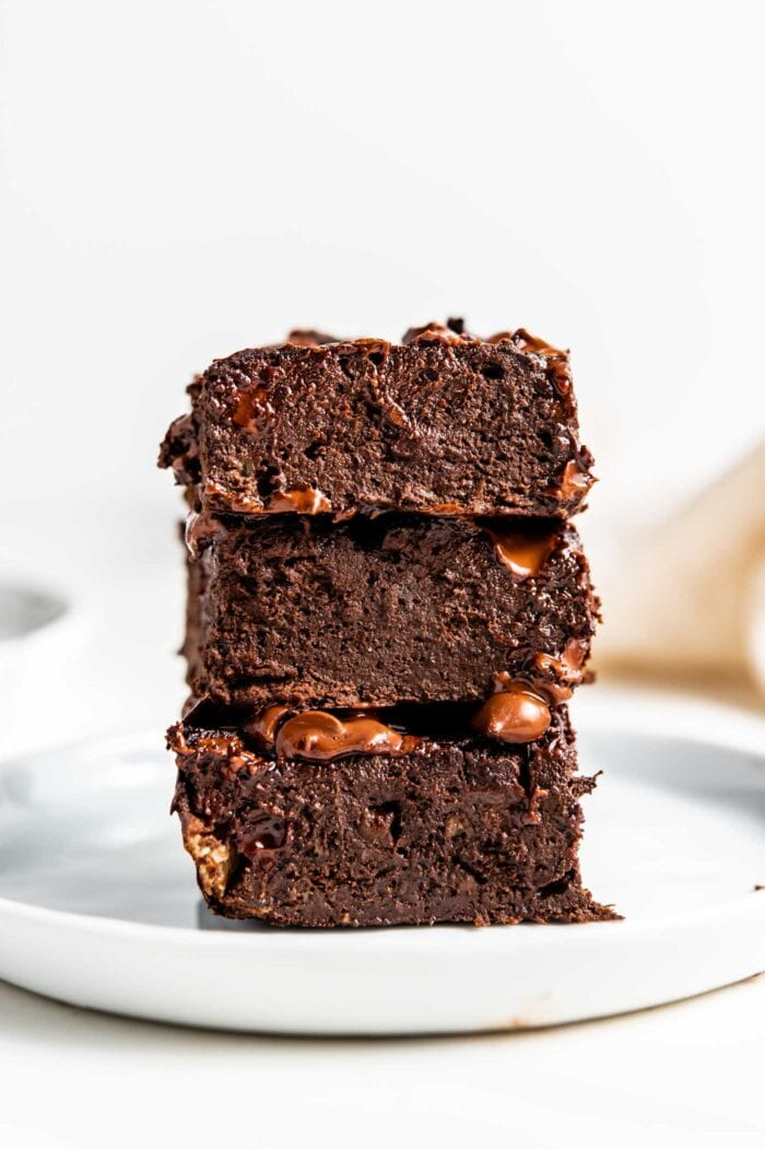Stack of 3 chocolate brownies on a small white plate.