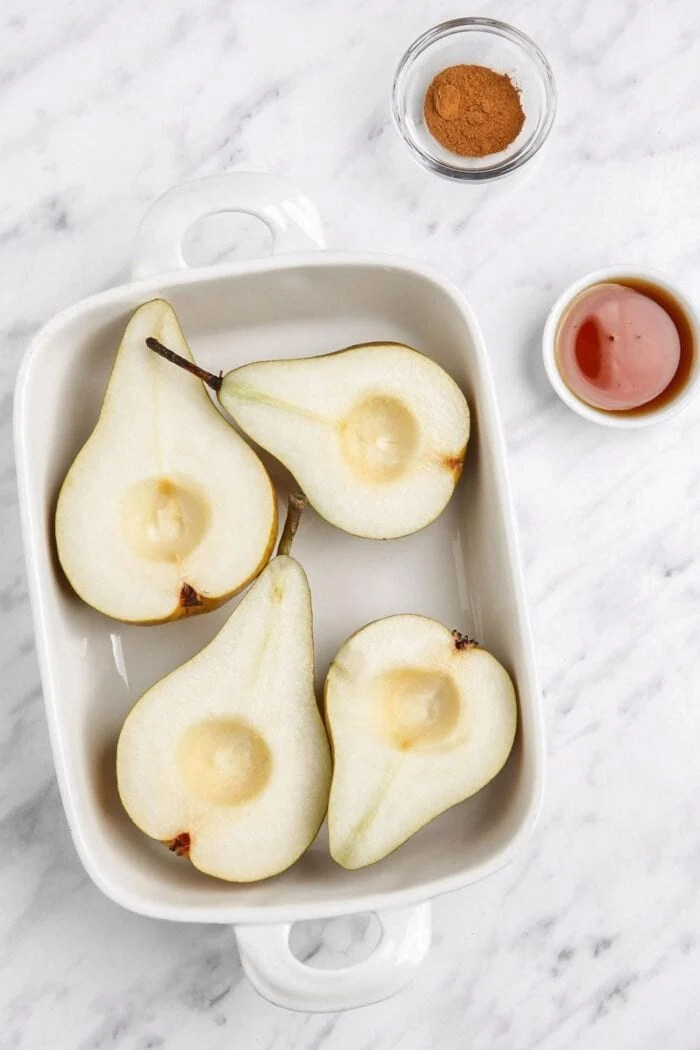 Sliced opens pears with seeds removed in a baking dish.
