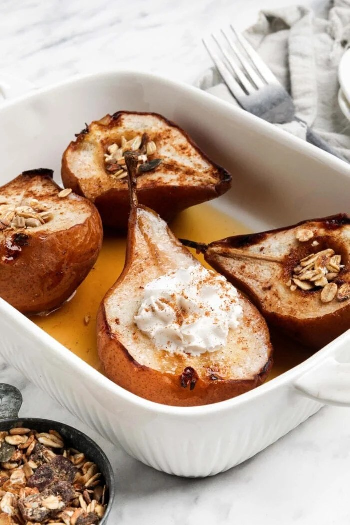 4 halves of baked pears topped with maple syrup and whipped cream in a baking dish.