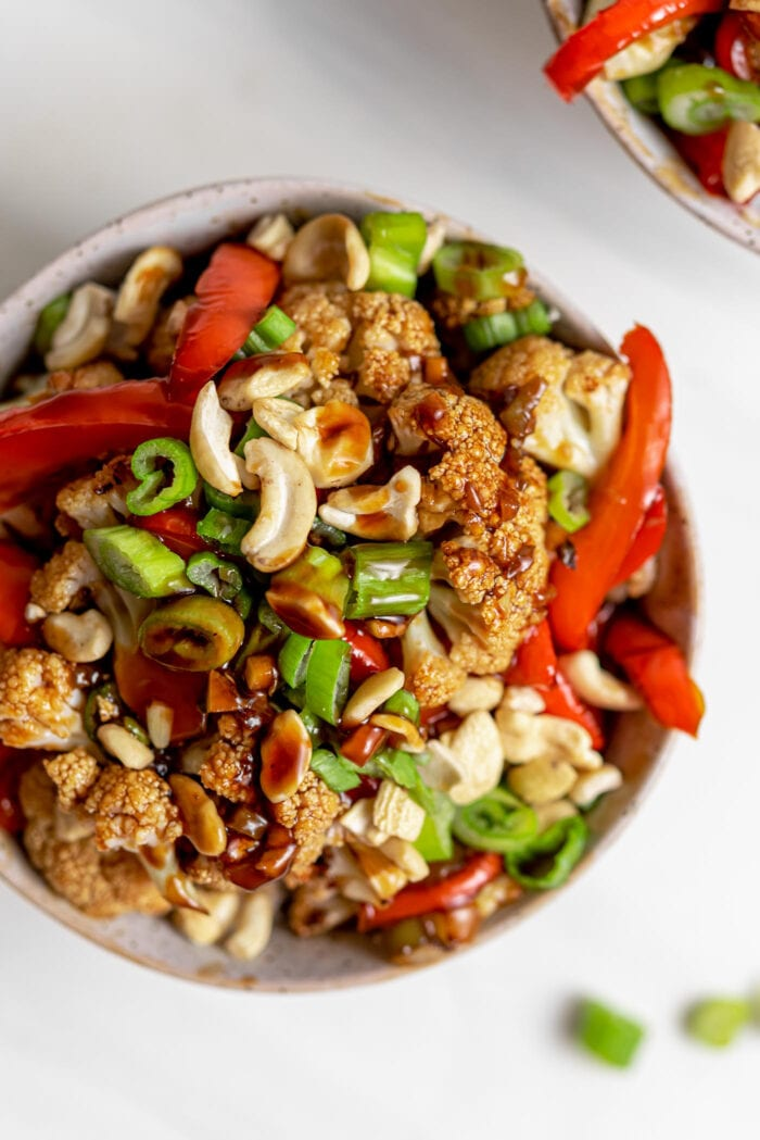 Overhead view of a bowl of kung pao cauliflower with bell peppers, green onion and cashews