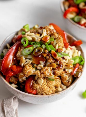 Bowl of cauliflower kung pao topped with chopped green onions and cashews.