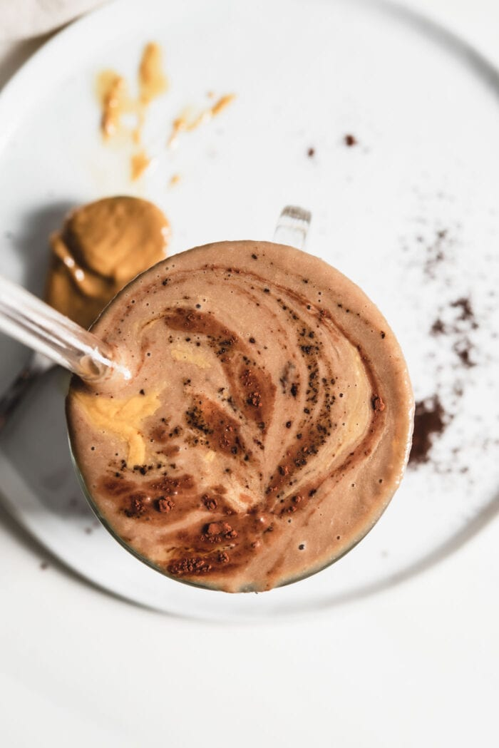Overhead view of a chocolate smoothie sprinkled with cinnamon in a glass.