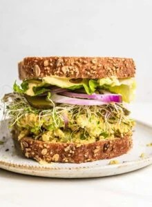 Close up view of a chickpea salad sandwich with onion, lettuce and sprouts.