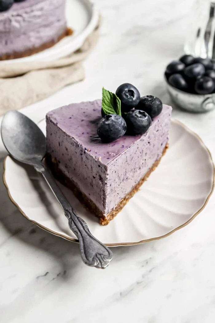 Slice of blueberry cheesecake on a small plate with a spoon.
