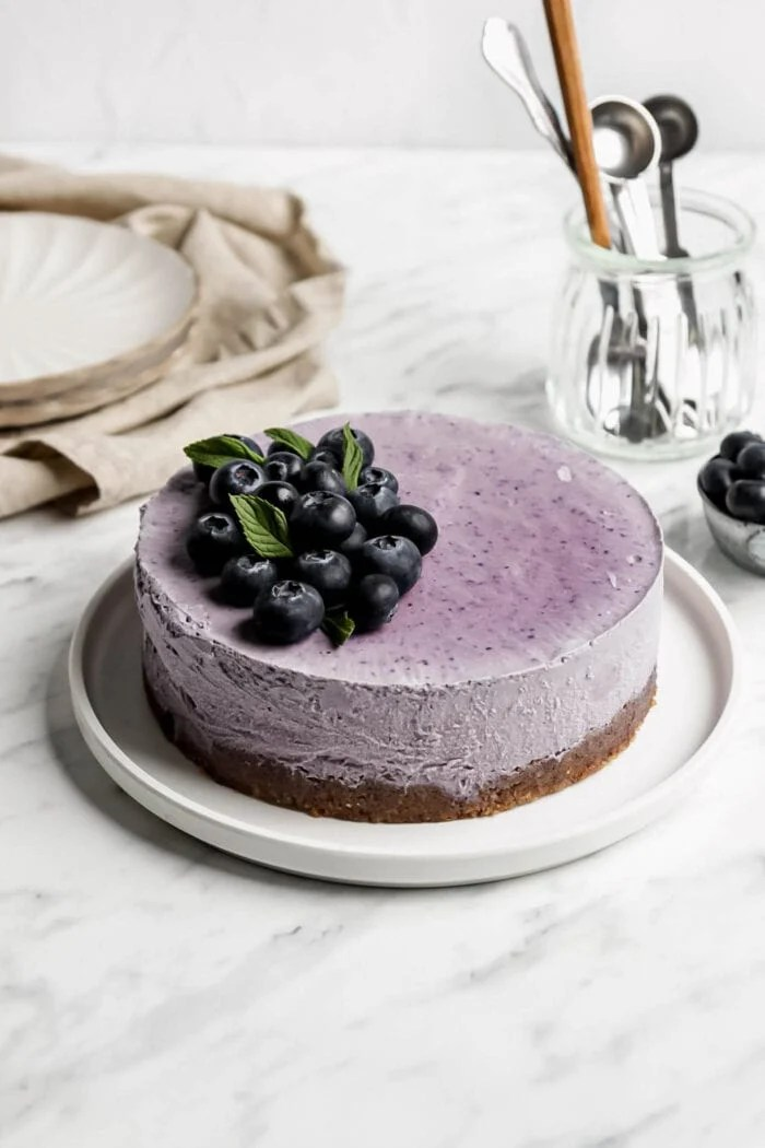 Blueberry cheesecake topped with blueberries on a plate.