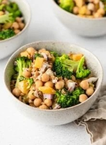 Bowl of chickpea salad with broccoli, farro, bell peppers and red onion. Two more bowls in background.