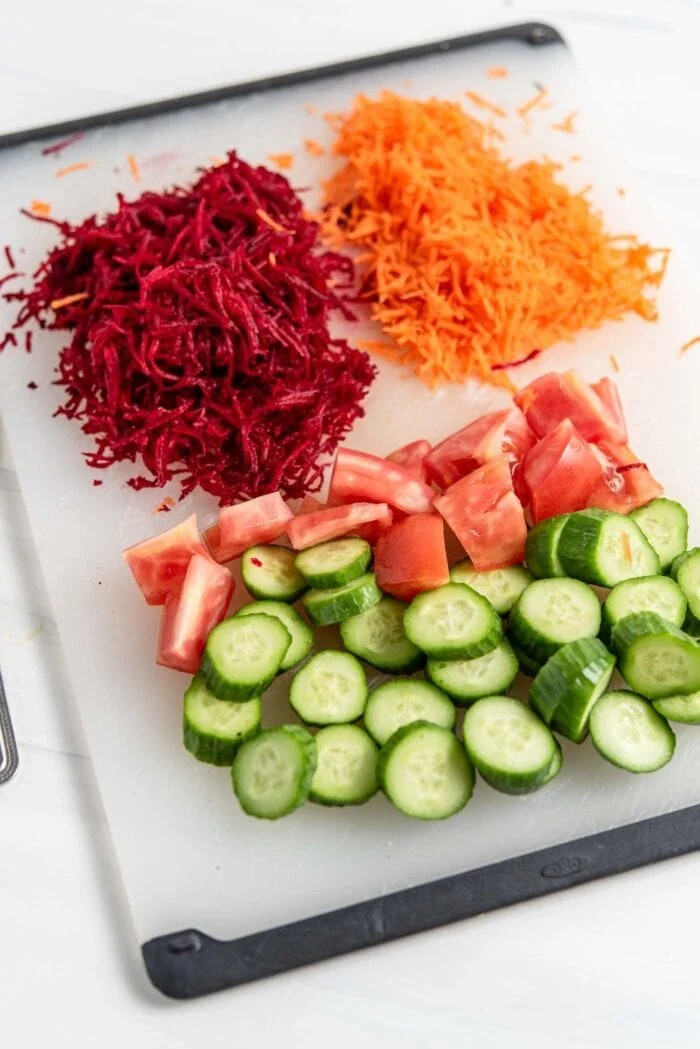 Chopped cucumber, chopped tomato, grated beet and carrot on a cutting board.