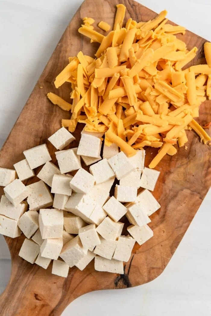 Cubed tofu and grated cheese on a cutting board.