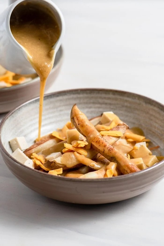 Pouring gravy over baked fries, tofu and cheese in a bowl.