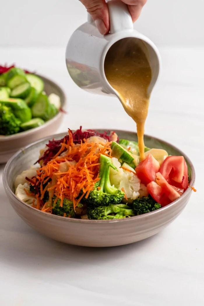 Pouring gravy over a colourful bowl of vegetables.