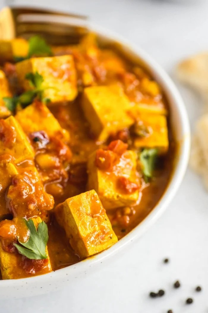 Close up of tofu in a creamy tikka masala sauce in a bowl.
