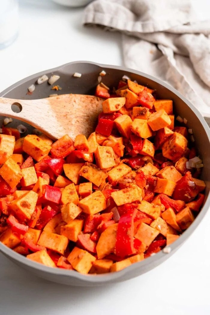 Sweet potato and bell pepper cooking in spices in a skillet.