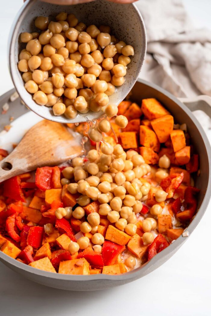 Dumping a bowl of chickpeas into a skillet of sweet potato and bell pepper.