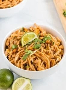 Vegetarian pad thai in a bowl topped with cilantro and a slice of lime.