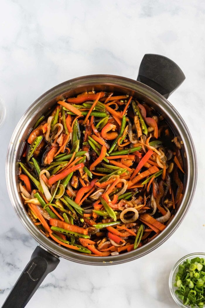 Stir fried vegetables cooking in a large frying pan.