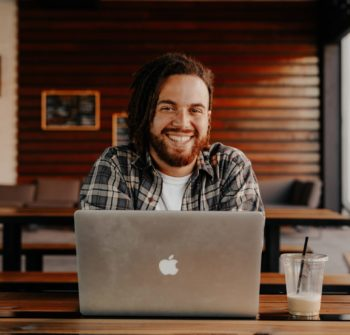 man in black and white striped polo shirt sitting on chair in front of silver macbook