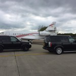 Two Landrover Discoveries in front of a private jet at Teesside International Airport