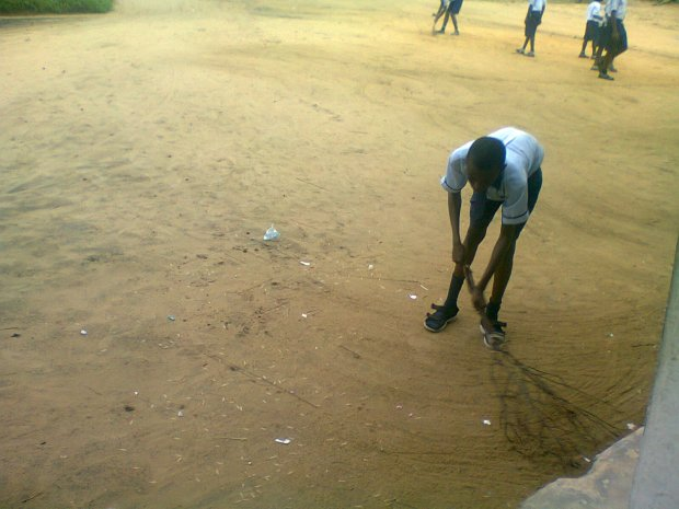 Creative broom? Students sweep the school compound before Assembly commenced in a rural school.