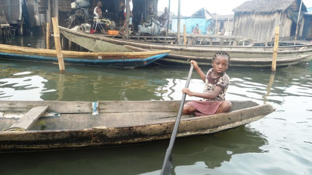 A young girl paddling canoe to the market.