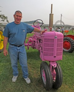 Chris Bailey, a USAF veteran, stands by a pink tractor at the Whitman county Fair.