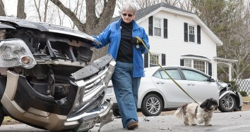 "Donna Martin, of Auburn, looks at the damage to the front of her vehicle as she walks her dog Molly away from the accident she was involved in at the corner of Montello Street and Central Avenue Monday morning. ""I was going to pick up my friend's buddy and there is that shrub I couldn't see past. I waited for one car to go past, but didn't see him. The male driver of the vehicle she hit, background, was taken to the hospital with non life threatening injuries."