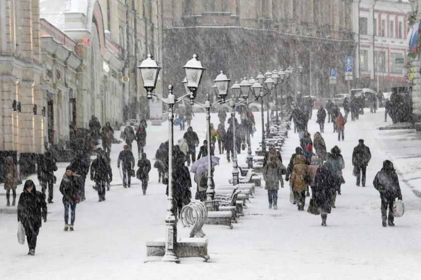 People walk during snowfall in Moscow