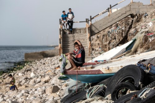 A Palestinian boy sits on a boat on the beach on May 14, 2016 at the al-Shati refugee camp in Gaza City.
