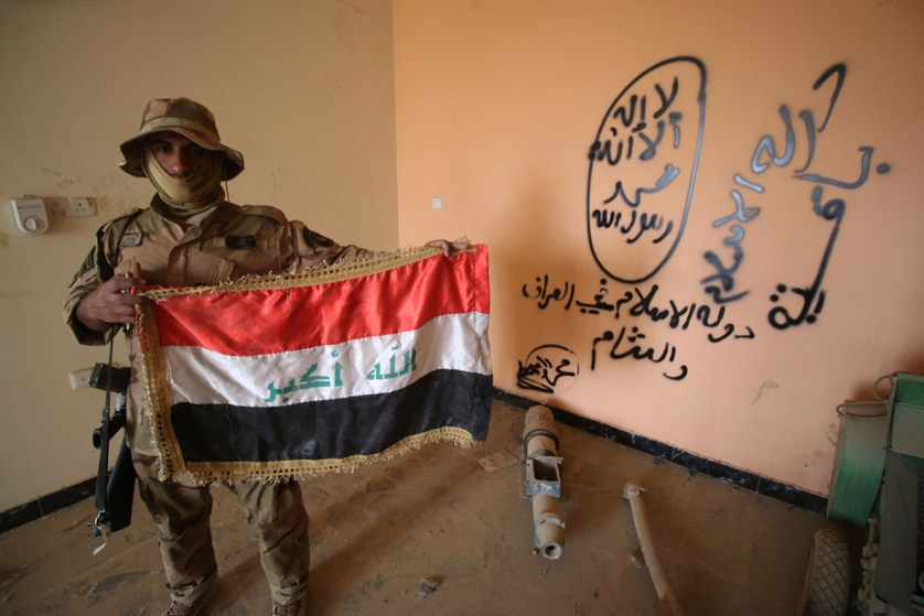 A member of the Iraqi pro-government forces holds his national flag in a building bearing Daesh graffiti in the al-Dhubat II neighbourhood of Fallujah