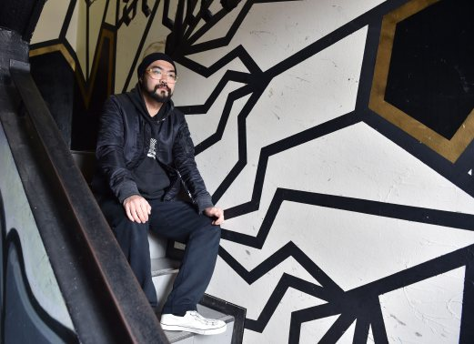 This picture taken on February 25, 2016 shows Japanese street artist Kohei Yamao, better known by his nom d'artiste BAKIBAKI, posing with his work in Tokyo. Beneath the crackle and hum of Tokyo's neon veneer, a city that once viewed graffiti art as mindless vandalism could be set for an anarchic facelift. / AFP PHOTO / KAZUHIRO NOGI / TO GO WITH AFP STORY: Japan-art-social, INTERVIEW by Emily Shen -----RESTRICTED TO EDITORIAL USE - MANDATORY MENTION OF THE ARTIST UPON PUBLICATION - TO ILLUSTRATE THE EVENT AS SPECIFIED IN THE CAPTION------