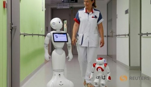 "A nurse walks with ""Pepper"" (L) and ""Zora"" the robots, humanoid robots designed to welcome and take care of visitors and patients, at AZ Damiaan hospital in Ostend, Belgium June 16, 2016."