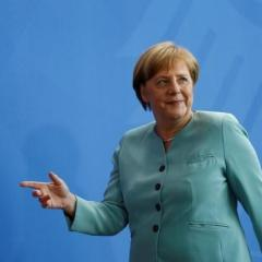 Merkel says Russia sanctions no end in themselves, but implementing peace deal is key