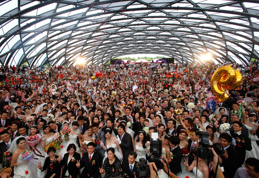 Couples pose for a group photograph during a mass wedding ceremony at the Taipei Flora Expo Hall in Taiwan on 9 September 2010