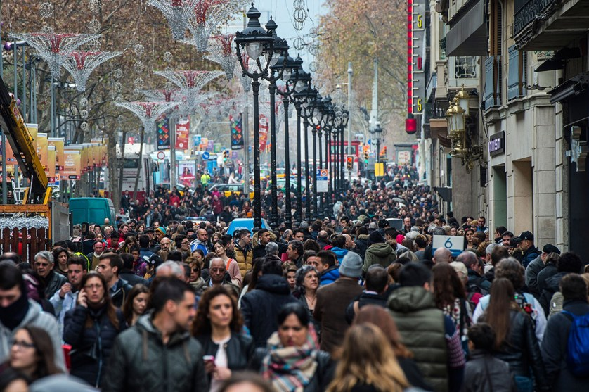 People walk along a crowed shopping street on the first day of the winter sales in Barcelona, Spain