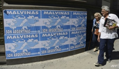"""File photo of people walking past posters that read, """"The Malvinas (Falklands Islands) are Argentine"""" in downtown Buenos Aires, on Mar 31, 2016"""