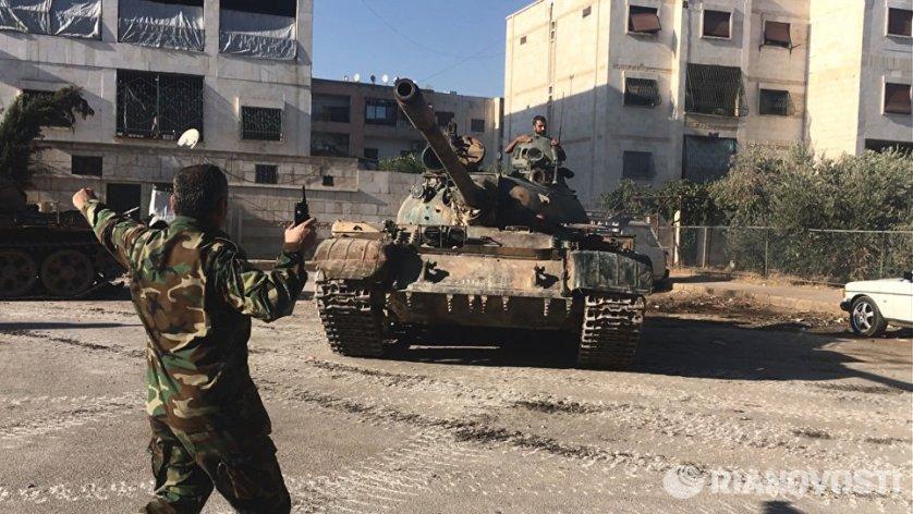 Бойцы сирийской армии во время наступления в районе училища тыла на юго-западе Алеппо в Сирии.