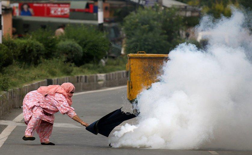 Женщина пытается потушить горящую канистру со слезоточивым газом во время протестов в Кашмире, Индия.